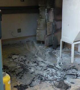 Figure 1 is a color photo of an enclosed room. In one corner of the room, two sets of metal lockers (each is 3 doors high) are blackened from fire. In the middle of the floor, a layer of ashes and partially consumed components are visible. The walls of the room do not appear damaged.