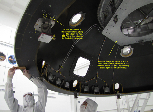 Figure 3, apparently photographed from the floor level, shows two ESD-robed technicians in a high bay cleanroom performing measurements on the lower rim of a saucer-shaped structure that is apparently suspended above a floor. An arrow extends from a text note to a set of inserts on the underside of the rim in proximity to a coiled spring with a square plate on its free end. Another arrow extends from a text note to a large metal plate suspended beneath the center of the underside of the saucer.